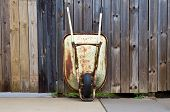 image of wheelbarrow  - An old rusty wheelbarrow leaned up against a wooden fence - JPG
