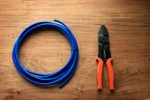 foto of wire cutter  - Cable or wire and a wire cutter or crimping pliers on a wooden work desk - JPG