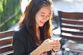 image of handphone  - A portrait of a Young businesswoman work oudoor in a cafe - JPG