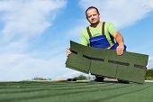 picture of shingles  - Man installing bitumen roof shingles  - JPG