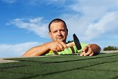 stock photo of shingles  - Man finishing installing the bitumen roof shingles  - JPG