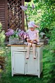 image of dress-making  - adorable child girl in pink plaid dress making lilac flower wreath in spring garden - JPG