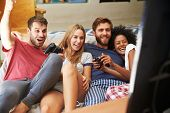 stock photo of pajamas  - Group Of Friends Wearing Pajamas Playing Video Game Together - JPG
