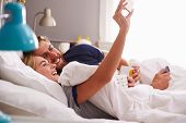 stock photo of two women taking cell phone  - Young Couple Lying In Bed Taking Selfie On Mobile Phone - JPG
