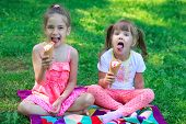 stock photo of tease  - Kids girls friends children eating ice cream and teasing showing off tongues - JPG