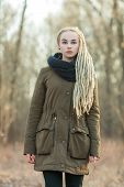 pic of dread head  - Young beautiful blonde hipster woman in scarf and parka with dreadlocks hairstyle posing on a blurry forest background - JPG
