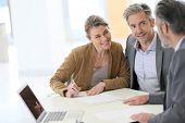 foto of contract  - Mature couple signing financial contract at the bank - JPG