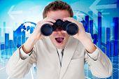 picture of binoculars  - Positive businessman using binoculars against global business graphic in blue - JPG