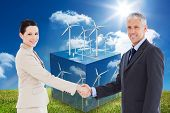 image of turbines  - Smiling business people shaking hands while looking at the camera against wind turbines on cube showing more wind turbines - JPG