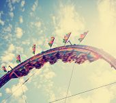 image of carnival ride  -  a fair ride at dusk toned with a retro vintage instagram filter effect  - JPG