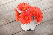 pic of pitcher  - Orange gerbera flowers in pitcher on wooden table - JPG