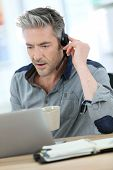 stock photo of stressless  - Mature man teleworking from home with laptop  - JPG