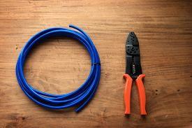 image of wire cutter  - Cable or wire and a wire cutter or crimping pliers on a wooden work desk - JPG