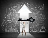 picture of keyhole  - Young businesswoman and keyhole at background lifting big key above head - JPG