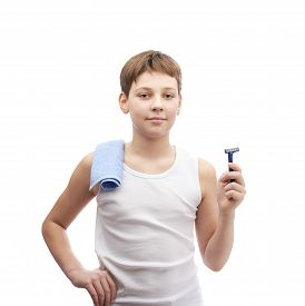 stock photo of shoulder-blade  - Happy young boy in a sleeveless white shirt with a towel over his shoulder and and a shaving razor blade in his hand - JPG