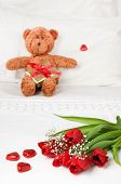 stock photo of teddy-bear  - Flowers for Valentines day on crisp white bed linen with little teddy bear with present on pillow - JPG