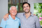 Portrait of smiling father and son with arm around wile standing at home poster