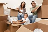 African American family, parents and son, unpacking boxes and moving into a new home, The adults are