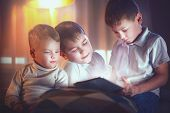 Three kids using tablet pc in bedroom at night. Brothers with tablet computer in a dark room. Childr poster
