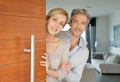 Couple opening house front door to welcome people in poster