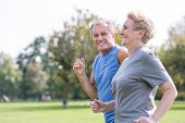 Happy senior man looking at woman while jogging in park poster