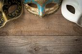 Three Venetian Carnival Masks For Mardi Gras Parade On Wooden Table poster