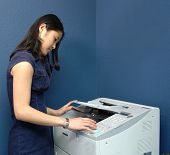 A young Asian girl working at a busy office fax machine.