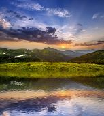Mountain View At Sunset. Panorama Of Green Grassy Valley, Woody Foggy Mountains Peaks With Snow Patc poster