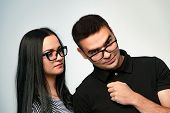 Serious Loving Brunette Woman In Eyeglasses Examines Her Boyfriend Looking At Camera. Tender Girl In poster