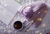 Flat Lay Composition With Cup Of Hot Beverage, Knitting Yarn And Book On Fuzzy Rug. Winter Evening poster