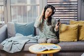 Cheerful Woman Listening To Music With Large Headphones And Singing.enjoying Listening To Music In F poster