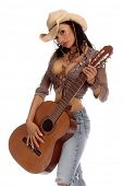Picture of super sexy rodeo cowgirl in torn jeans, boots and cowboy hat with a nylon string acoustic guitar.