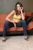 image of wife-beater  - Pretty young Mexican woman in jeans and a yellow wife beater casually sitting on a black and orange couch - JPG