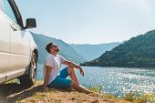 Young Man Sitting Near Suv Car At Seaside With Beautiful View Of Sea Bay With Mountains. Road Trip poster