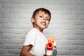Angry Little Boy With Grimaсe Of Fury On His Face Holding Toy Plastic Machine Gun poster