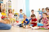 Kindergarten Children Playing Different Musical Toys. Early Musical Education In Day Care Centre poster