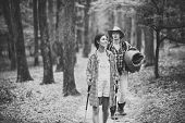 Couple In Love Hiking In Forest With Touristic Equipment, Trees On Background, Defocused. Tourists C poster