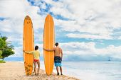 Beach surfers watching waves. Surfing lifestyle. Two people couple standing with longboards on hawai poster