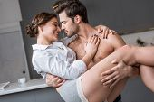 Passionate Man Holding In Arms Smiling Girlfriend At Home poster