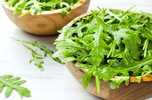 Fresh Green Arugula Leaves On Wooden Bowl, Rucola Salad On White Wooden Rustic Background With Place poster