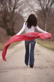 image of beautiful brunette woman  - pretty young brunette woman walking away with red shawl - JPG