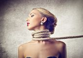 stock photo of strangling  - beautiful woman kidnapped with rope around the neck - JPG