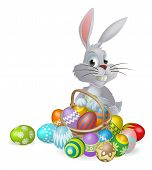 foto of ester  - An Easter bunny white rabbit with a basket of painted chocolate Easter eggs - JPG