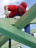 stock photo of purlin  - Carpenter taking measurement of house rafter beam - JPG