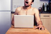 stock photo of masturbate  - Young Naked Man Watching Porn In His Kitchen - JPG