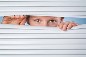 picture of snoopy  - A young woman peeking through closed venetian blinds or shutters - JPG