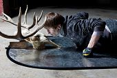 stock photo of black tail deer  - Young man lying down looking at the deer skull in a dark basement - JPG