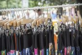 stock photo of thrift store  - clothes on a rack on a flea market - JPG