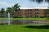 picture of florida-orange  - Looking across a pond towards a three story apartment complex in Naples Florida - JPG