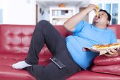 picture of obese man  - Overweight man eats pizza while watching tv at home  - JPG